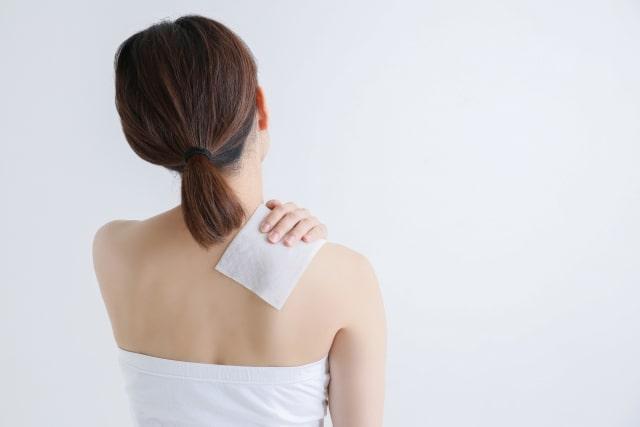 湿布を貼る女性